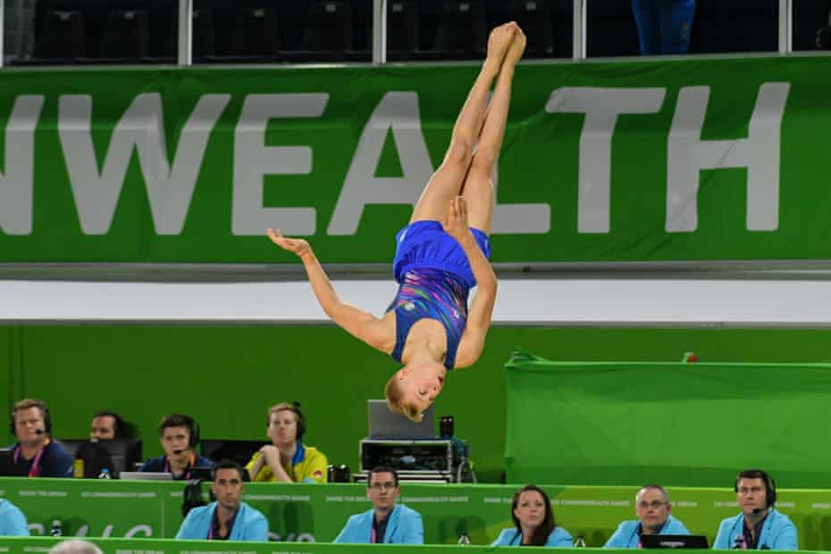 A gymnist flys through the air during competition