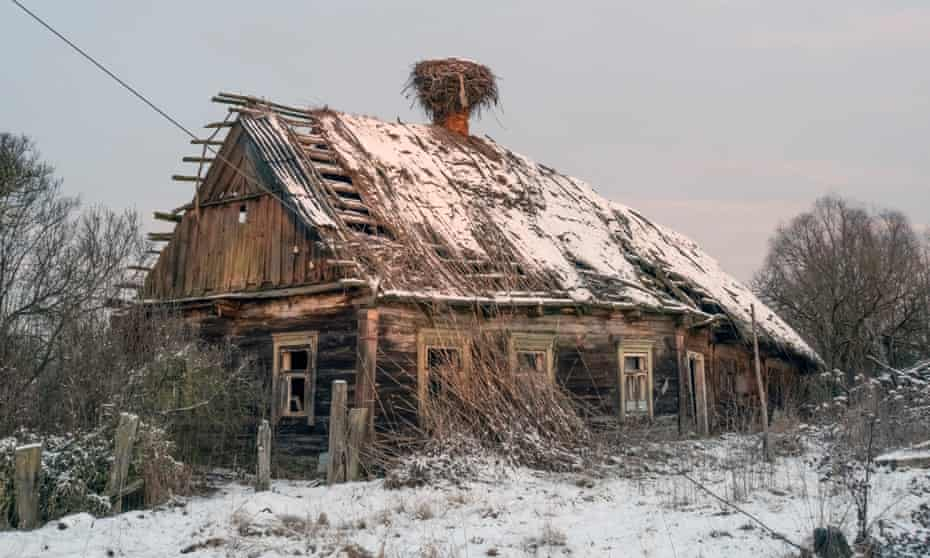 An empty White Stork nest rests on the chimney of an abandoned home in Kudrychy.