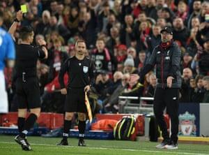 Referee Carlos del Cerro Grande, left, shows a yellow card to Liverpool's manager Jurgen Klopp.