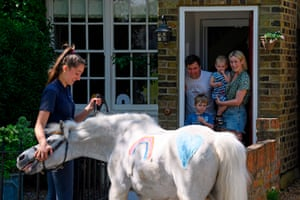 "Twickenham, UKAlice Blant, with her brother Stanley and parents Paul and Bryony, receives a visit from Welsh mountain pony Annie's Wizz with handler Daisy Cinque. Park Lane Stables are taking the fun to peoples' windows during lockdown in an initiative called ""Tiny pony at your window"""