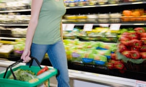 A woman in a grocery store produce aisle with shopping basket