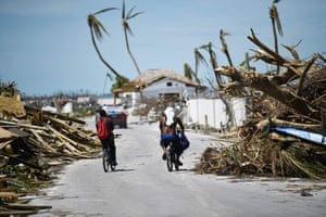 Residents pass damage caused by Hurricane Dorian on 5 September, in Marsh Harbour, Great Abaco Island in the Bahamas