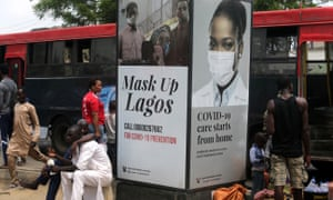 People walk past a billboard that reads: 'Mask up Lagos'