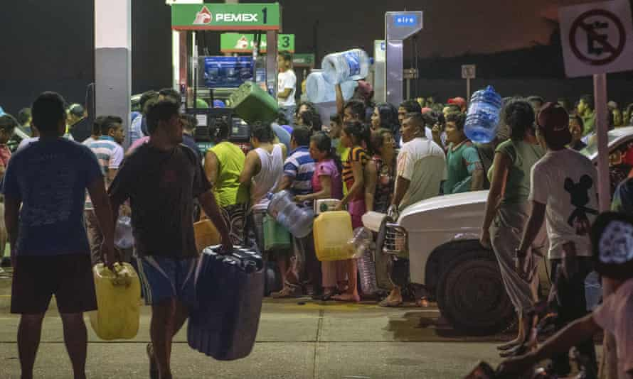 Residents steal gasoline and diesel from a gas station following protests against an increase in fuel prices in Allende, southern Veracuz State, Mexico Tuesday.