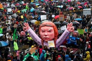 Participants in Düsseldorf, Germany, gather around a carnival float depicting Greta Thunberg