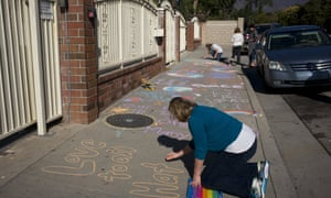 Karen Fagan, joined by her daughters, Kate and Elizabeth Bowman, writes chalk messages on the sidewalk outside the Islamic Center of Claremont in Pomona, California to show their support for Muslim communities on 25 November 2016.