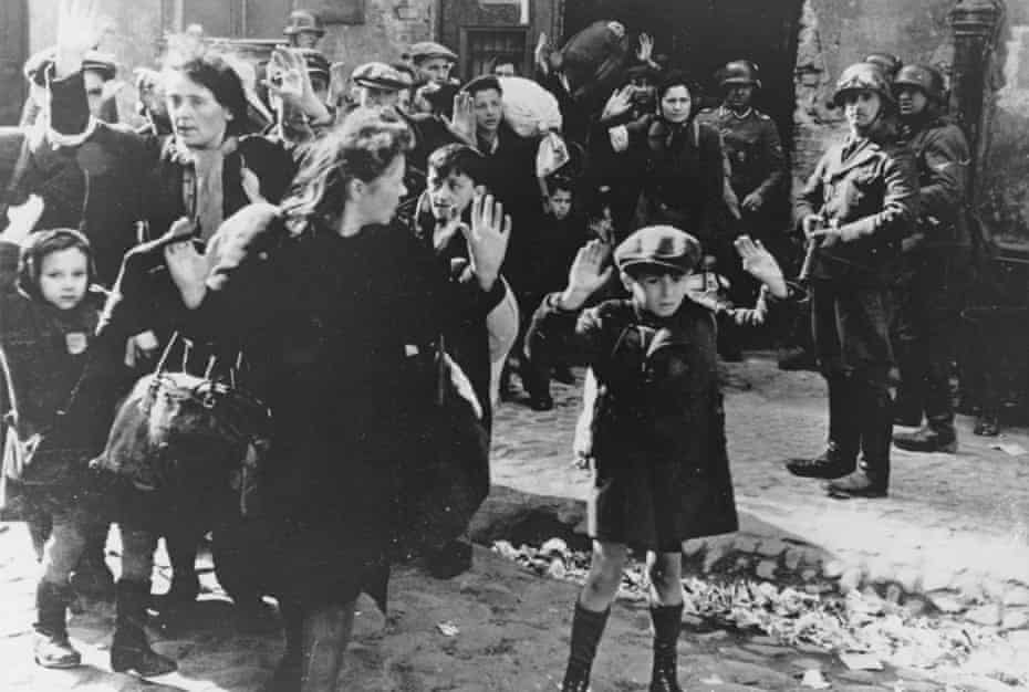A group of Jews, including a small boy, surrender to German soldiers following the collapse of resistance in the Warsaw Ghetto in 1943.