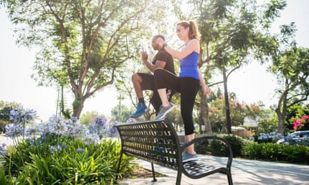Man and woman using a park bench for exercises