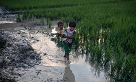 A young girl and a baby wade through mud after arriving in Bangladesh from Myanmar.