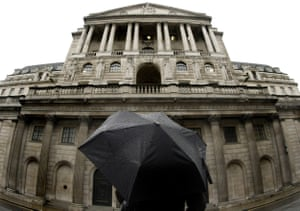 A woman with an umbrella waits to cross the street outside the Bank of England in London.