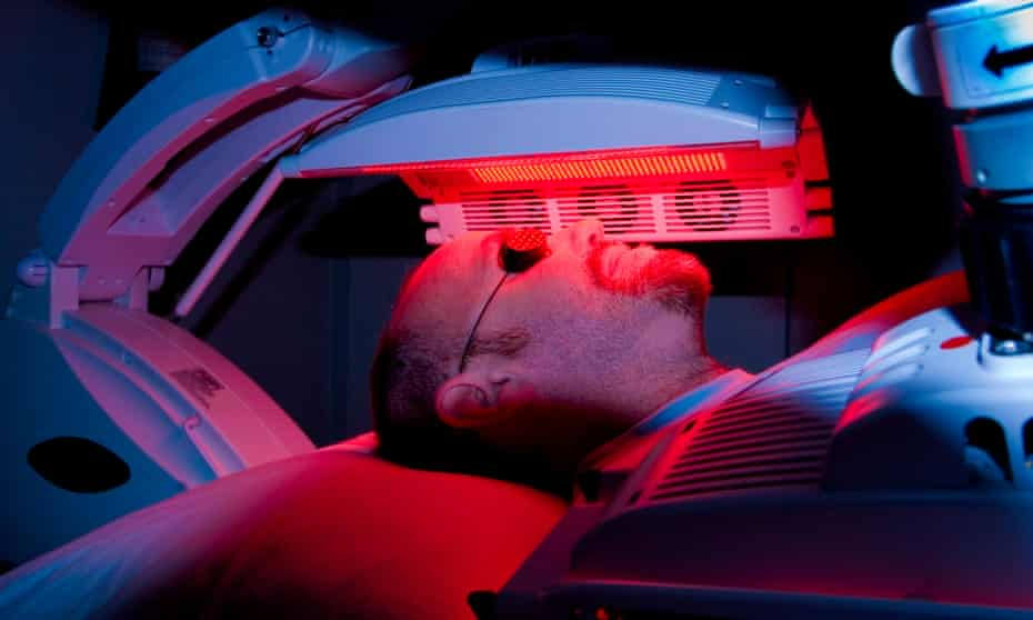 The face, with goggles over his eyes, and covered torso of a male patient lying on a bed with an LED red light machine hovering over his face