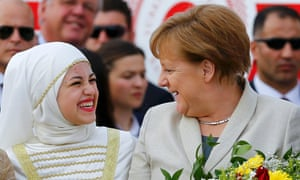 Angela Merkel talks to a refugee