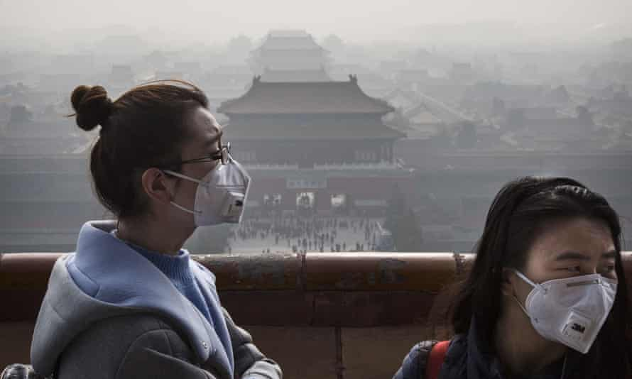 Chinese women wear masks as haze from smog caused by air pollution hangs over the Forbidden City in Beijing.