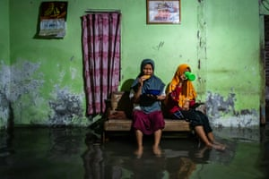 Parmini and her granddaughter Anisa have their Ramadan evening meal in their flooded home in Demak.