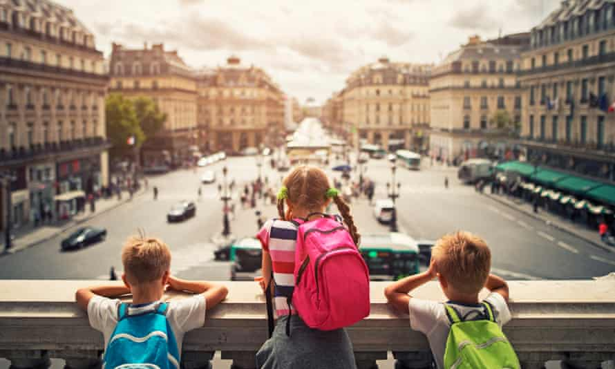 Three kids visiting Paris. They are looking from the balcony of Paris Opera at the place de l'opera. The girls is aged 9 and her brothers are aged 6.