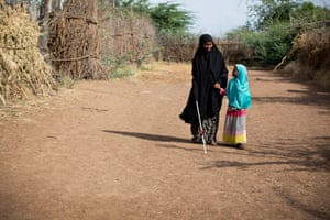 A child guides Hussein along a road at the camp