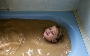Talita Cohen, four, poses in a bath filled with tap water from the Darling River in Louth, New South Wales, Australia