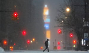 A man walks along West 59th street in New York City in falling snow.