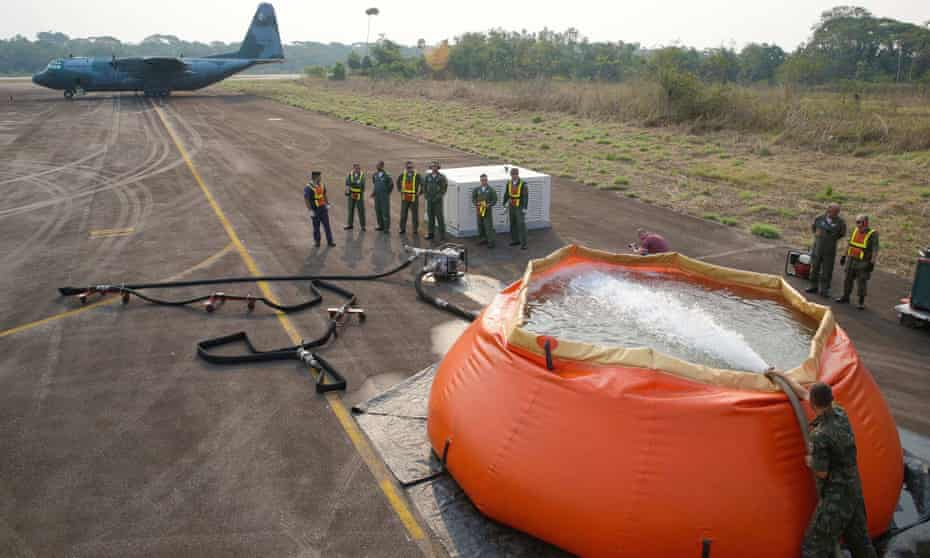 A Brazilian air force Hercules C-130 waiting to collect bags of water to fight fires in the Amazon rainforest on Saturday