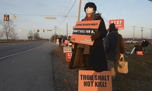 A woman holds a sign to protest the execution of Lisa Montgomery.