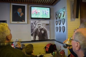 In the Shannon RFC clubhouse next to the stadium, Munster fans watch the Leicester v Ulster match on a TV placed above a picture of the famous Munster and Shannon player Gerrry 'Ginger' McLoughlin and the shields won by the club for winning the All-Ireland League.