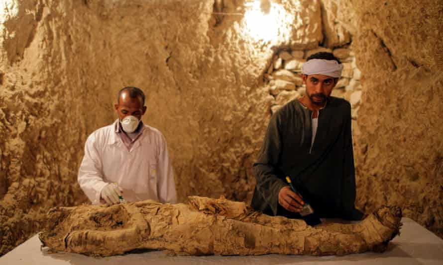 Egyptian archaeologists with a newly discovered mummy at Luxor'.