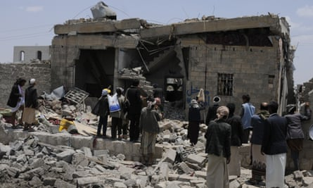 People gather around a heavily damaged building after airstrikes on Arhab, Yemen.