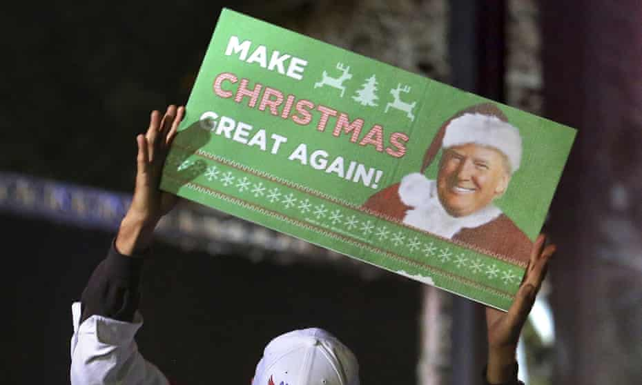 A supporter of President-elect Donald Trump holds up a Christmas-themed sign at a rally in Orlando. Those who are not fans of the president-elect are giving relatives gifts they might not love.