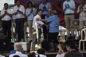 """Colombian president Juan Manuel Santos shakes hands with Rodrigo Londoño, alias """"Timochenko,"""" top commander of the FARC insurgent army, at a celebration for the completion of the FARC's disarmament."""