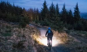Mountain biking with lights at dusk. Rear view of a man using bright lights to illuminate the mountain bike trail in front of him as daylight fades.
