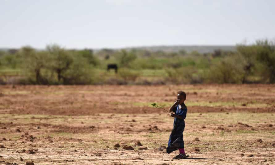 A girl stands in a barren field on the outskirts of Hargeisa, Somaliland.