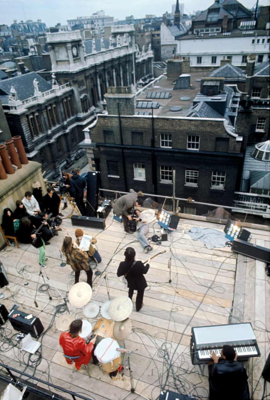 The band, joined by keyboardist Billy Preston (bottom right), on the roof of the Apple Corps building, 1969.
