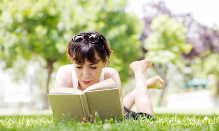 Young woman reading a book<br>young woman lying down reading a book in a park