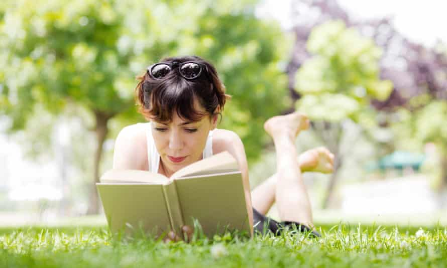 Young woman lying down reading a book in a park