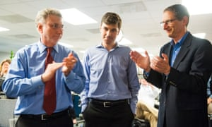 Washington Post reporter Eli Saslow, centre, is feted by Washington Post Executive Editor Marty Baron and editor David Finkel after the Pulitzers are announced in the newsroom April 2014. The Washington Post via Getty Images's Eli Saslow won for explanatory writing and The Guardian US and The Washington Post via Getty Images (Barton Gellman) shared the honour for for Public Service.