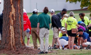 A spectator is treated by emergency medical staff after lightning struck the Tour Championship at East Lake, where the damage to a tree is clearly visible.
