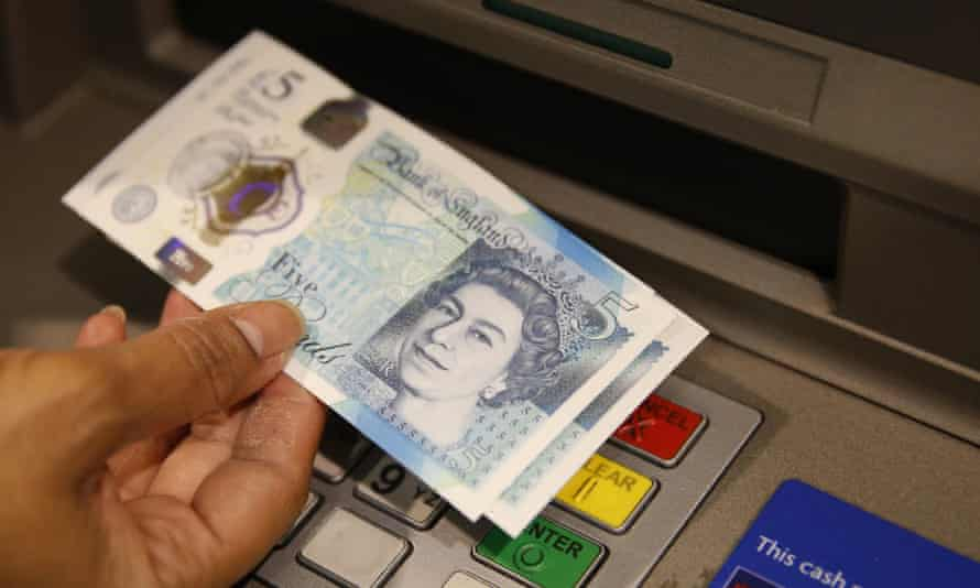 A person holds £5 notes at an ATM
