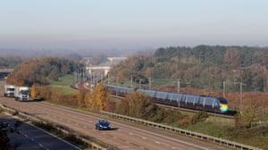A train passes a quiet M20 motorway in Ashford, Kent