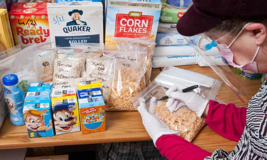 A volunteer labels breakfast cereal portions at the Hillingdon centre