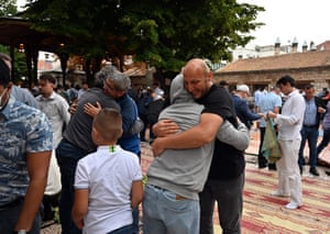 Bosnian Muslims share hugs after early morning prayer on Eid al-Adha, in front of Sarajevo's central, Gazi-Husref Bey's mosque
