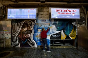 A shop owner closes the shutters of his stall next to portraits of Sheikh Farid al-Jabari, a senior clan leader in Hebron, and Hannah Szenes, a Jewish paratrooper in the second world war