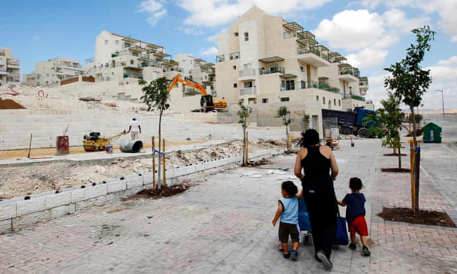 A woman walks with children past apartments under construction in the West Bank Jewish settlement of Maale Adumim.