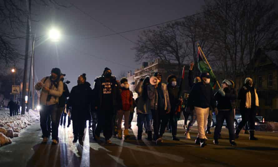 Demonstrators march on Tuesday in Kenosha, Wisconsin following the announcement that no charges would be filed against the police officer who shot Jacob Blake.