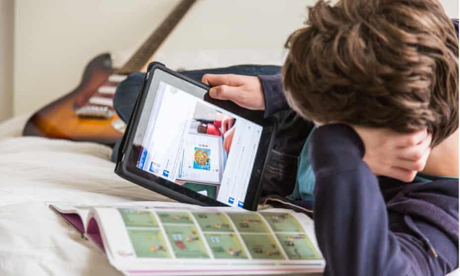 Teenage boy on tablet looking at Facebook