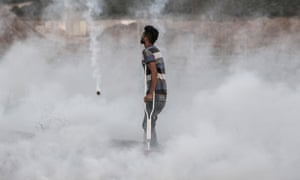 A Palestimnian protester in clouds of teargas.