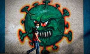 A boy walks past street art showing a coronavirus in Gaza city.