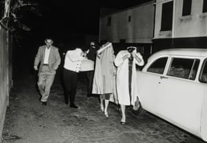 A group of prostitutes cover up after a vice squad raid at the Carolina Pines Restaurant on Melrose Avenue, 1957.