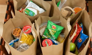 Brown bags, each holding five days worth of the government recommended lunches for a single child.