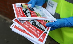 A volunteer holds leaflets while distributing them to residents of Halliwell in Bolton in the UK where the army has been brought in to help with surge testing.