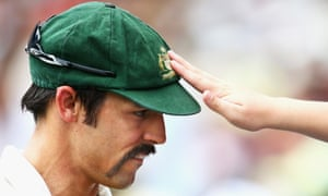 A fan reaches over the fence to touch former Australian paceman Mitchell Johnson's baggy green.